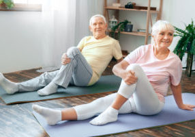 Senior man and woman doing yoga together indoors sitting turn aside leg stretching smiling